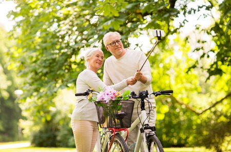 old photo: senior couple with bicycles taking selfie at park Stock Photo