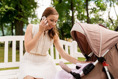 mother with stroller calling on smartphone at park Stock Photo