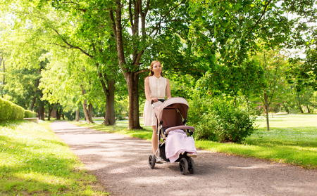 happy mother with child in stroller at summer park
