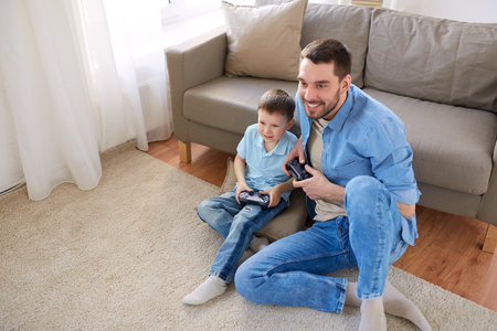 family sofa: father and son playing video game at home