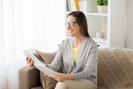 happy woman reading newspaper at home