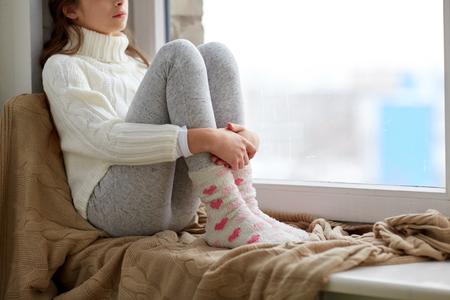 Niña sentada en el alféizar de la ventana en casa en invierno Foto de archivo - 86087695