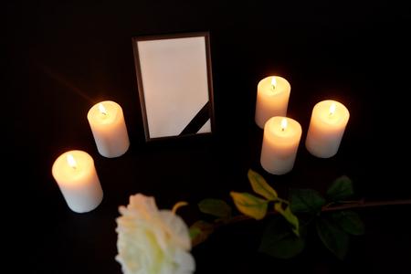 fotolijst met zwart lint, bloem en kaarsen Stockfoto