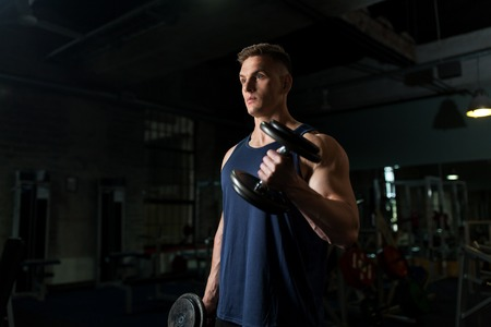 young man with dumbbells exercising in gym Stock Photo