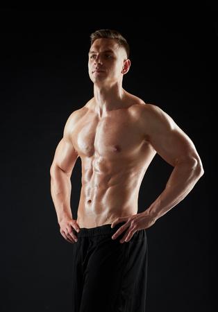 若い男や裸の胴体を持つボディービルダー 写真素材