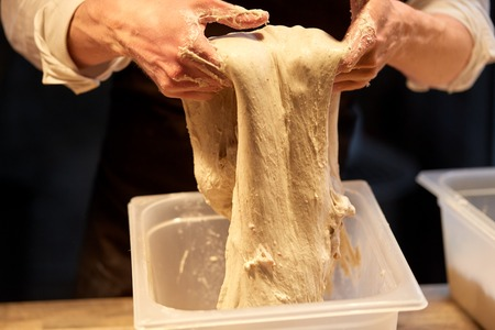 close up of baker hands making bread dough Banco de Imagens