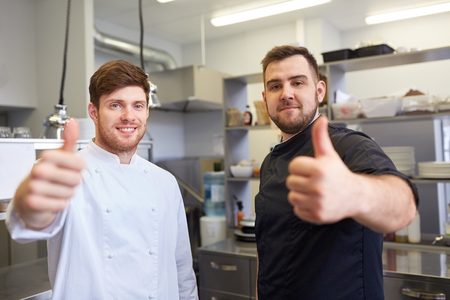 chefs at restaurant kitchen showing thumbs up