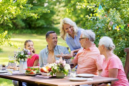 Famiglia felice avendo cena o festa di giardino estivo Archivio Fotografico - 86087843