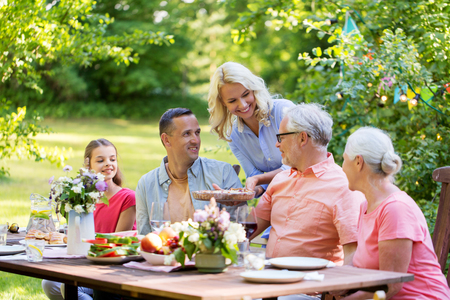 happy family having dinner or summer garden party Imagens