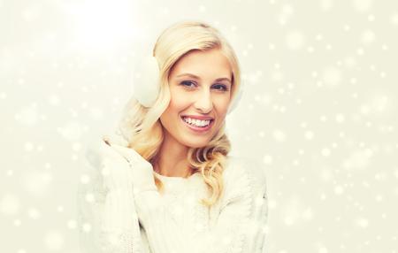 Sorridente giovane donna in inverno paraorecchie e maglione Archivio Fotografico - 86433493