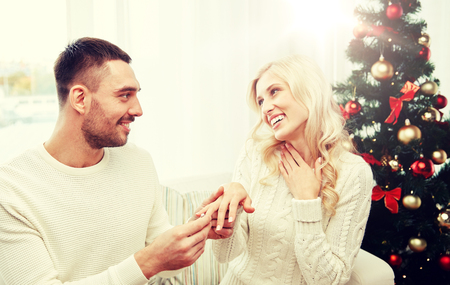 man giving engagement ring to woman for christmas Stock Photo