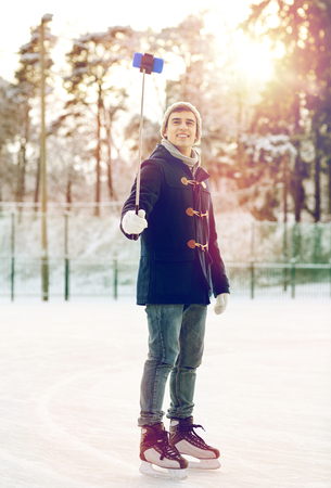 iceskates: happy young man with smartphone on ice rink