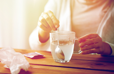 woman stirring medication in cup with spoon