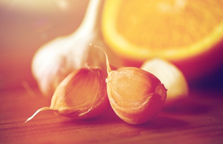 close up of garlic and orange on wooden table