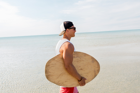 happy young man with skimboard on summer beach