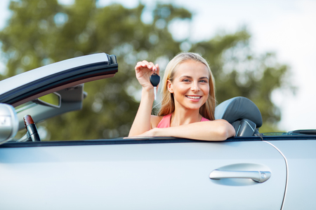 happy young woman with convertible car key