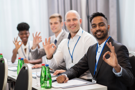 people at business conference showing ok hand sign Stock Photo