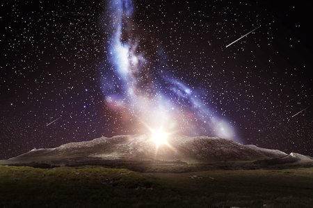 nature and astronomy concept - mountain landscape over night sky or space with shooting stars and galaxy background