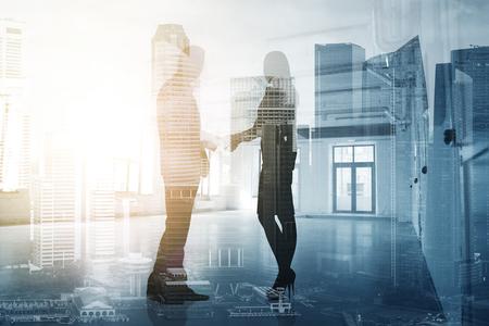 ビジネス、パートナーシップ、協力のコンセプト-ビジネスマンと実業家のシルエットが都市の背景に手を振る 写真素材