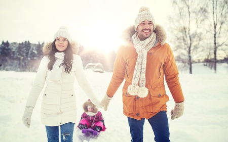parenthood, fashion, season and people concept - happy family with child on sled walking in winter outdoors Stock Photo