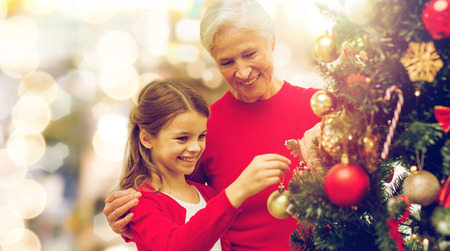 冬の休日、家族や人々のコンセプト-ライトの背景の上にクリスマスツリーを飾る幸せな祖母と孫娘