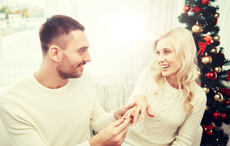 love, christmas, couple, present and people concept - happy man giving engagement diamond ring to woman at home Stock Photo - 86305506