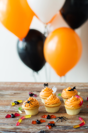 food, baking and holidays concept - cupcakes or muffins with halloween party decorations and jelly candies on wooden table and balloons