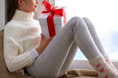 childhood, holidays and people concept - happy beautiful girl with christmas gift sitting on sill at home window