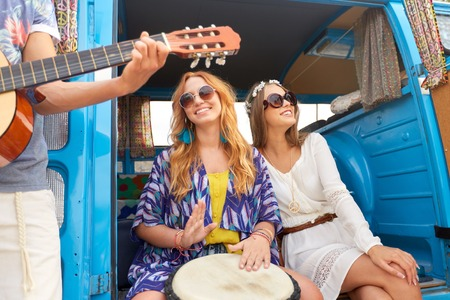 summer holidays, road trip, travel and people concept - happy young hippie friends with guitar and tom-tom drum having fun and playing music in minivan car