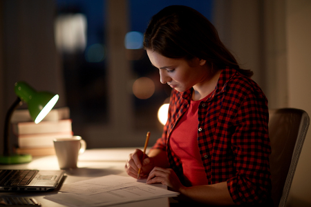 people, education, freelance and learning concept - woman or student girl with laptop computer writing to notebook at home at night Stock Photo