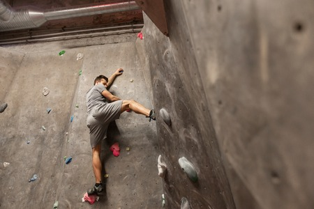fitness, extreme sport, bouldering, people and healthy lifestyle concept - young man exercising at indoor climbing gym wall