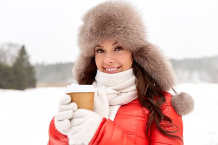 people, hot drinks and leisure concept - happy woman in winter fur with coffee cup hat outdoors Stock Photo