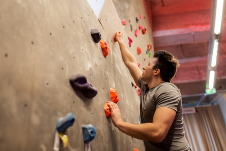 fitness, extreme sport, bouldering, people and healthy lifestyle concept - young man exercising at indoor climbing gym