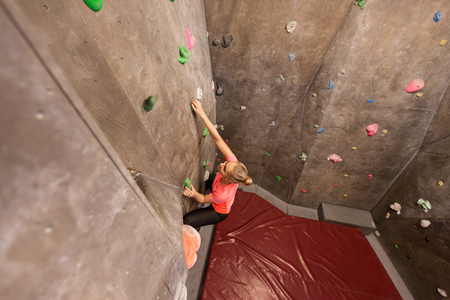 fitness, extreme sport, bouldering, people and healthy lifestyle concept - young woman exercising at indoor climbing gym Reklamní fotografie