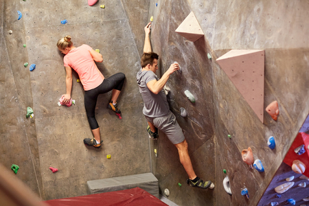 fitness, extreme sport, bouldering, people and healthy lifestyle concept - man and woman exercising at indoor climbing gym wall Stock Photo