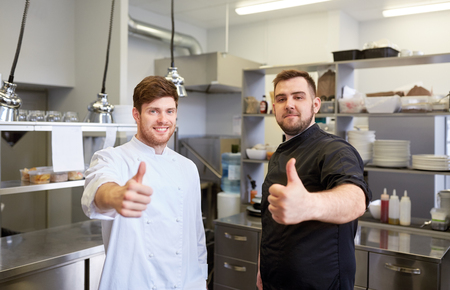 cooking, profession and people concept - happy male chef and cook at restaurant kitchen showing thumbs up Stock Photo