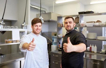koken, beroep en mensen concept - gelukkig mannelijke chef-kok en koken in restaurant keuken met duimen omhoog