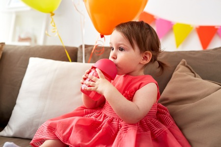 childhood, people and holidays concept - baby girl drinking from sippy cup or bottle at home birthday party Imagens