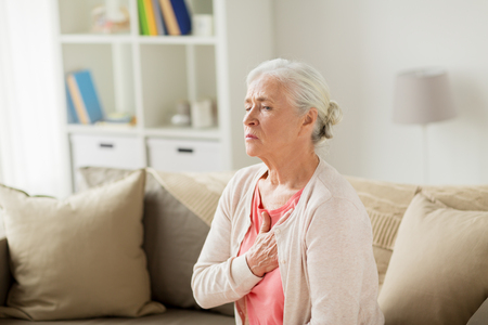 old age, health problem and people concept - senior woman suffering from heartache at home Imagens