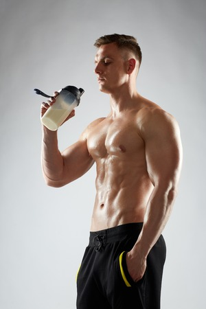 sport, bodybuilding, fitness and people concept - young man or bodybuilder with protein shake bottle and bare torso