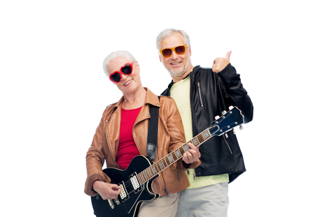 music, age and people concept - happy senior couple in sunglasses with electric guitar showing thumbs up