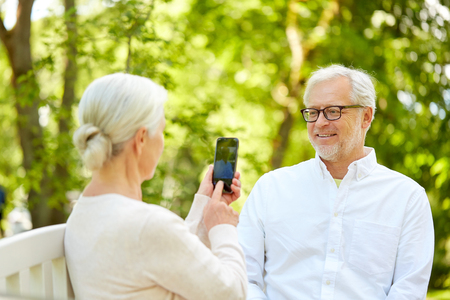 technology, retirement and old people concept - happy smiling senior couple with smartphone photographing in summer park