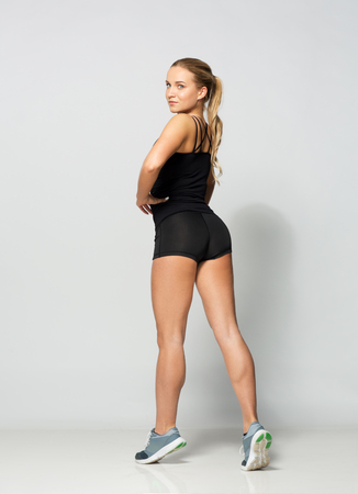 sport, fitness and people concept - young woman in black sportswear posing in gym Stock Photo