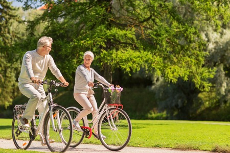active old age, people and lifestyle concept - happy senior couple riding bicycles at summer park Foto de archivo