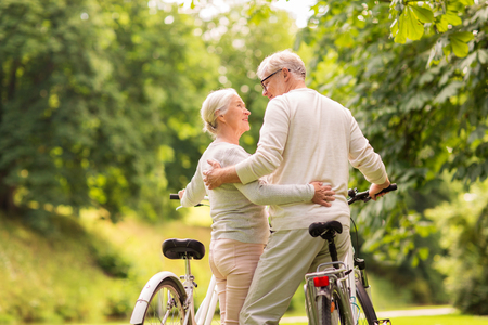 old age, people and lifestyle concept - happy senior couple with bicycles hugging at summer city park Stock Photo