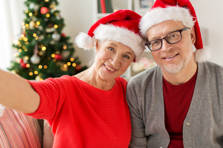 christmas, holidays and people concept - happy smiling senior couple in santa hats taking selfie at home