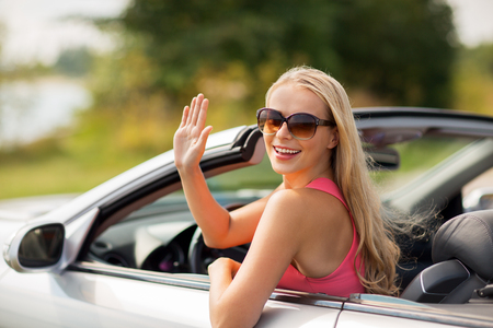 travel, road trip and people concept - happy young woman in convertible car waving hand Banco de Imagens - 86305815