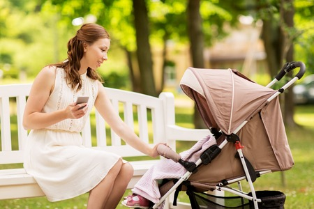motherhood, technology and people concept - happy mother with smartphone and baby girl stroller at summer park Stock Photo