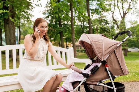motherhood, technology and people concept - happy mother with baby girl in stroller calling on smartphone at summer park Stock Photo - 86305836