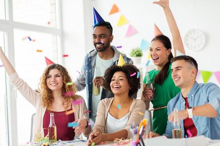 bedrijfs-, feest- en vakantie concept - gelukkig team met confetti en kronkel met plezier op kantoor verjaardagspartij
